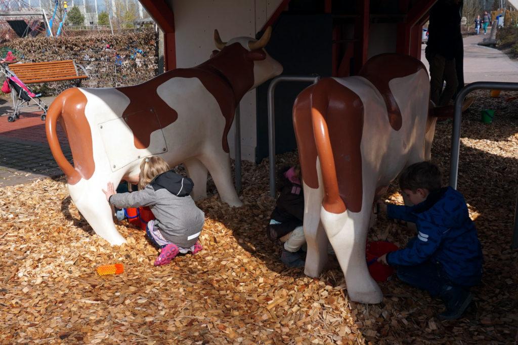 Die Kinder melken die Kühe während die Eltern produktiv arbeiten.