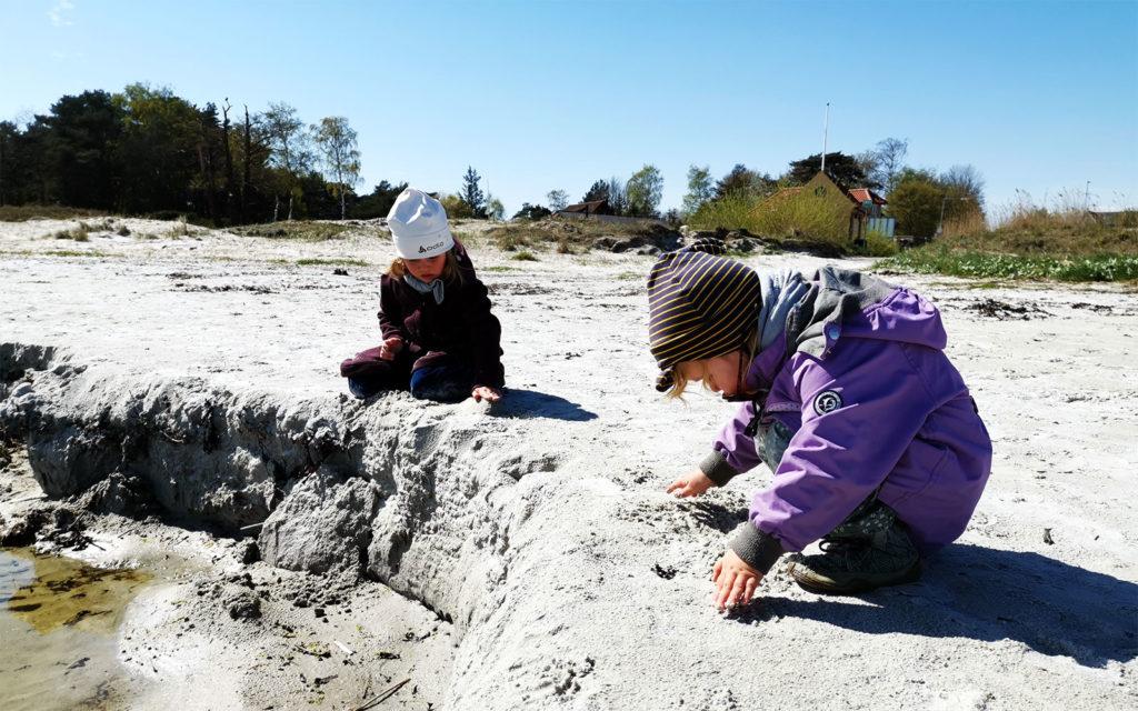 Die Kinder buddeln im kalten Sand der Ostsee.