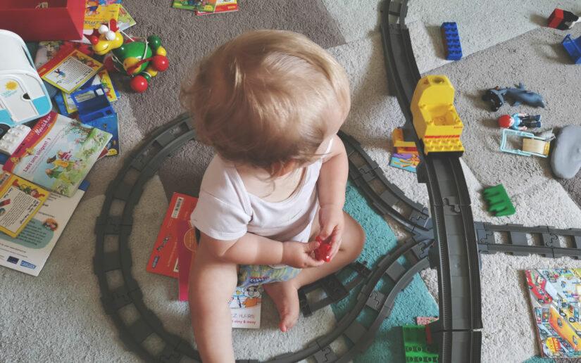 Kind sitzt im Kinderzimmer zwischen Spielzeug und Eisenbahn