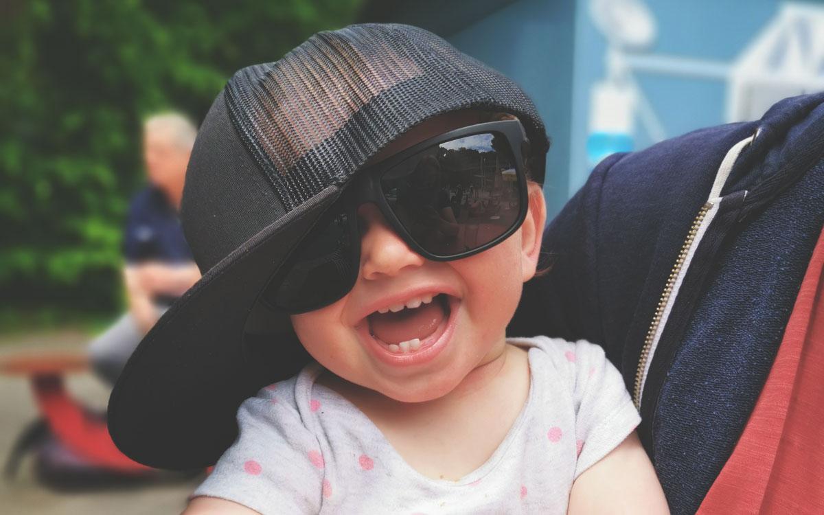 Lachendes Kind mit Sonnenbrille und Baseball-Cap