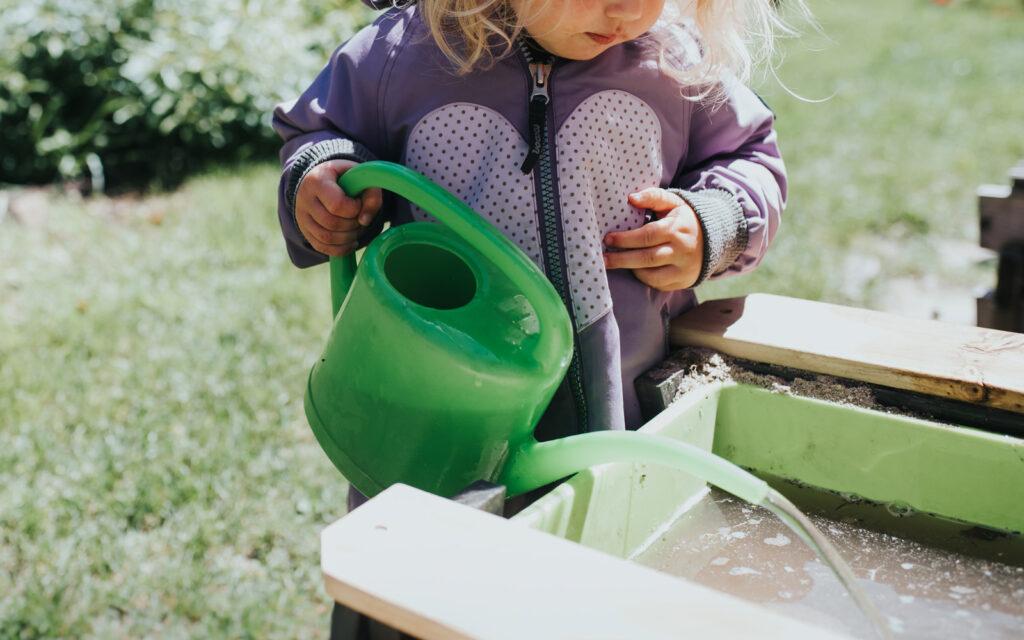 Kind gießt mir Gießkanne